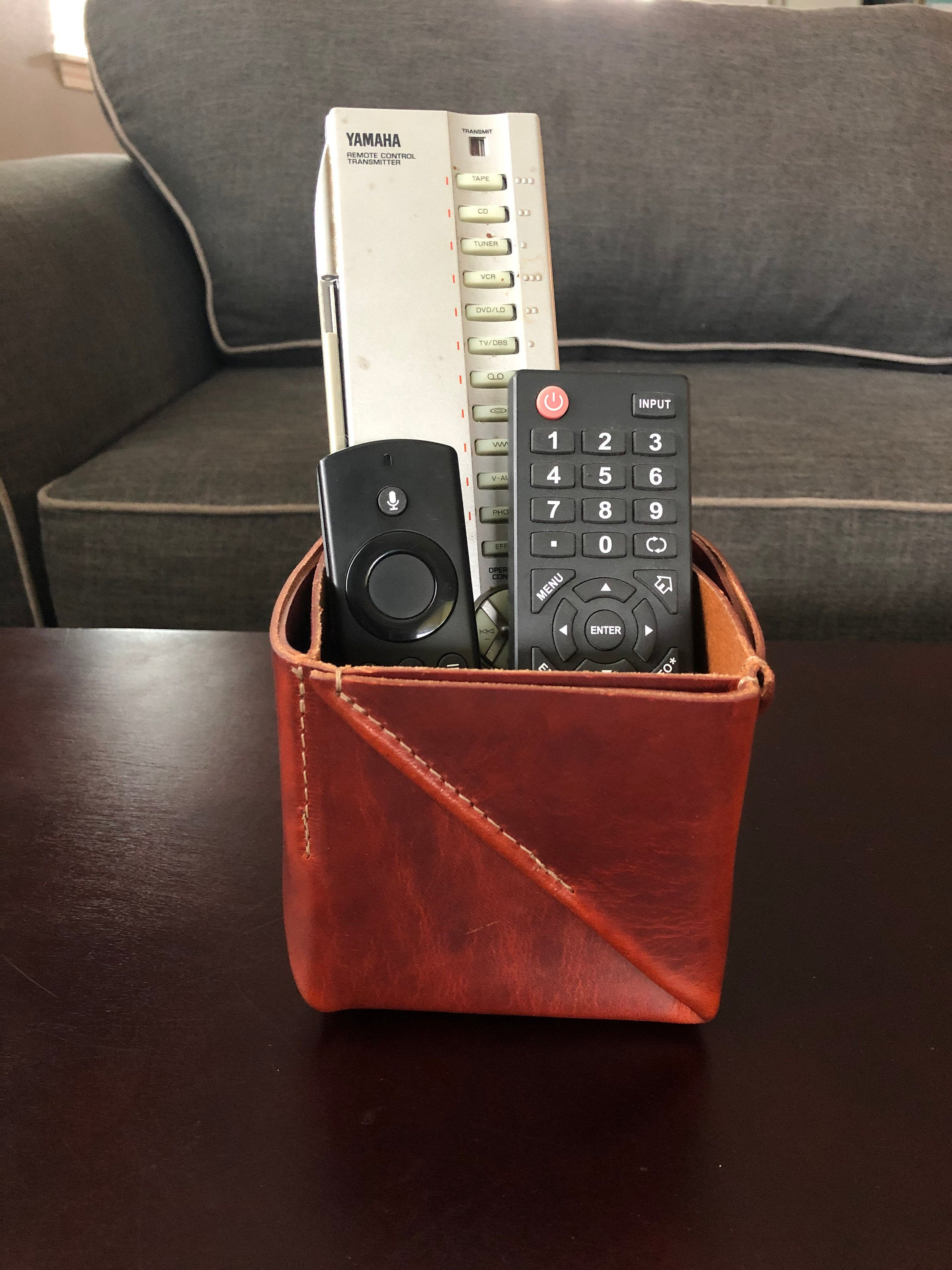 Brown folded leather box holds remotes in living room