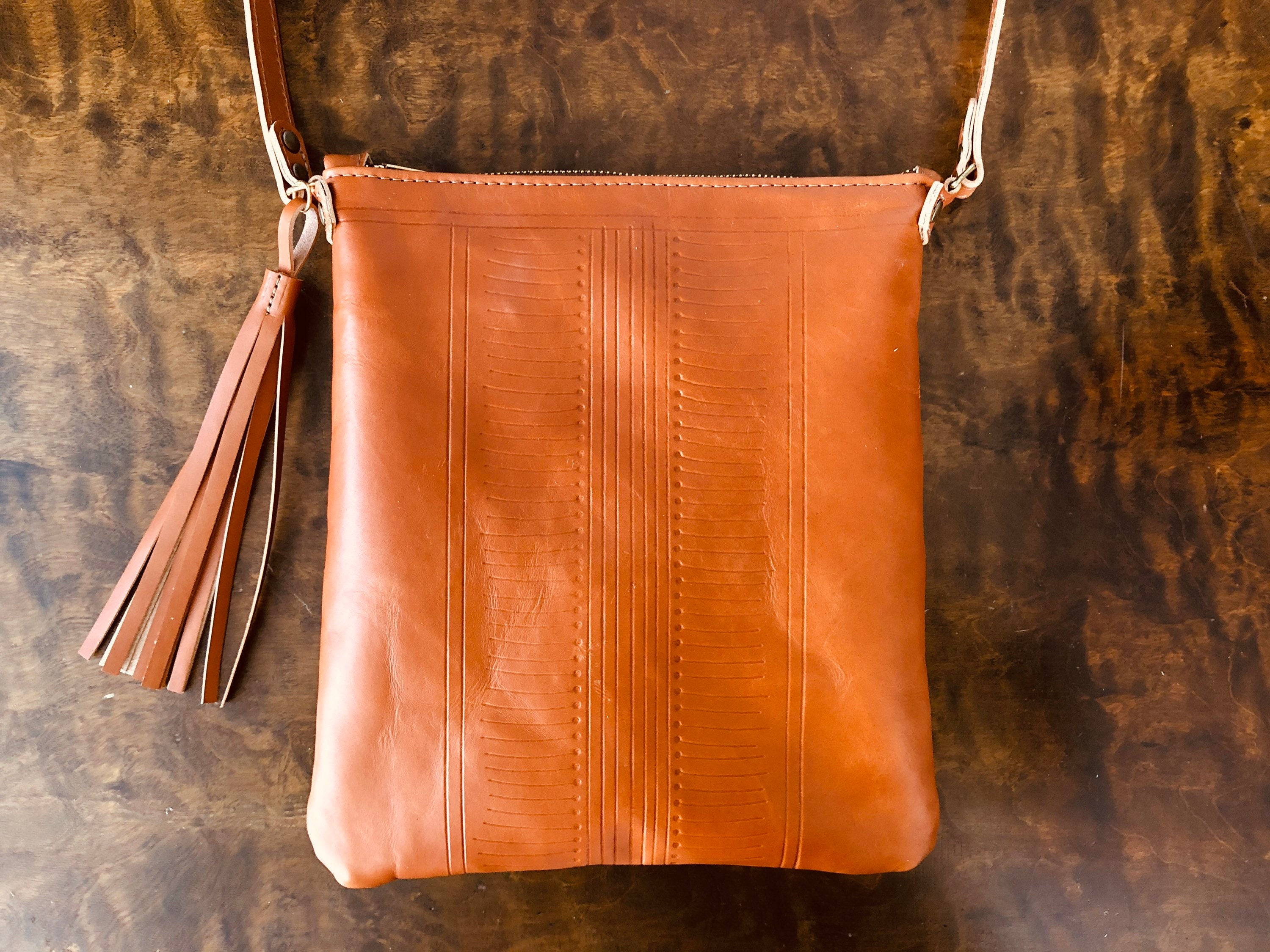 Tan leather crossbody pouch with pattern detail and tassel rests on dark brown table