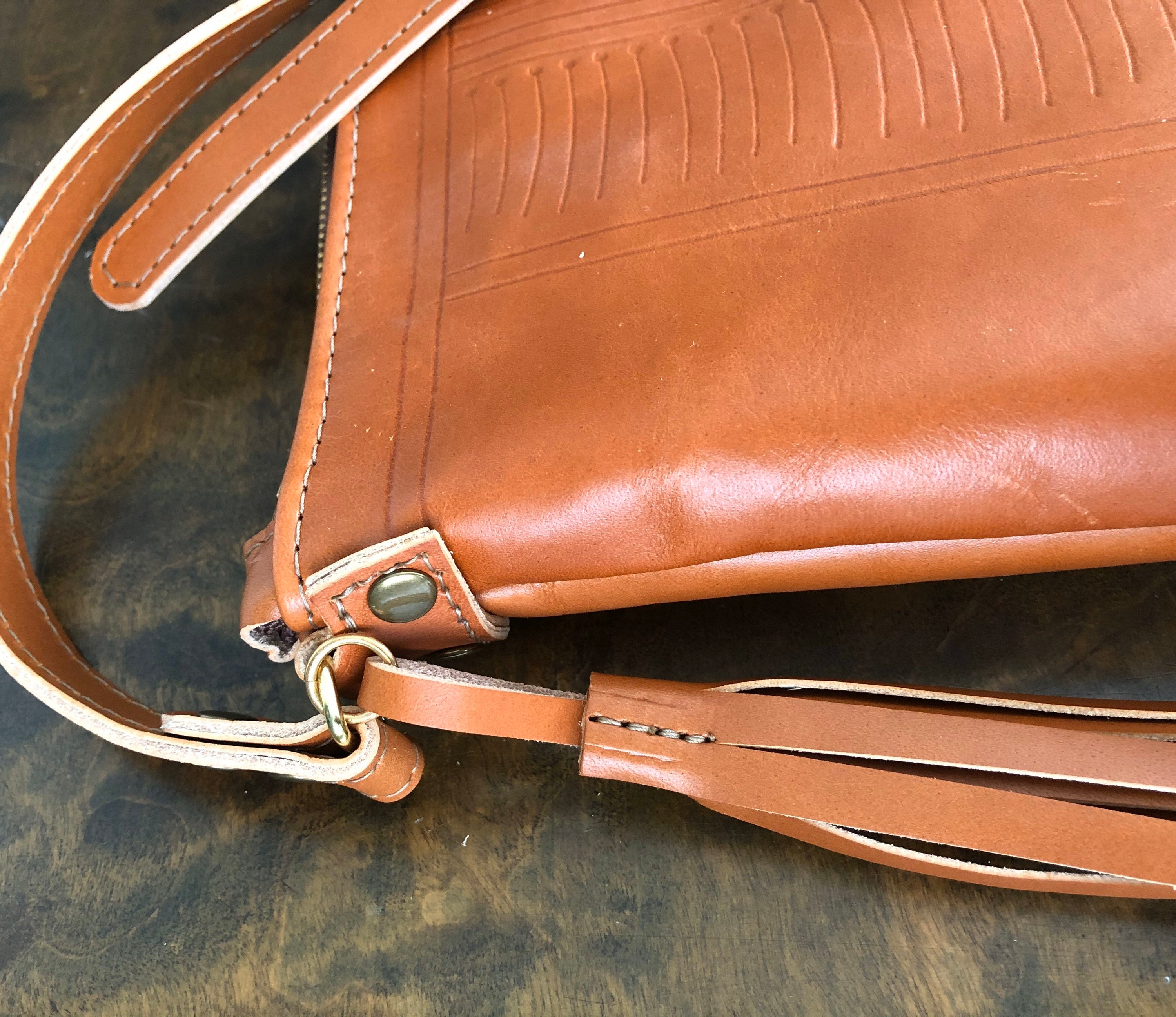 Close up of crossbody strap and tassel on side of tan pouch