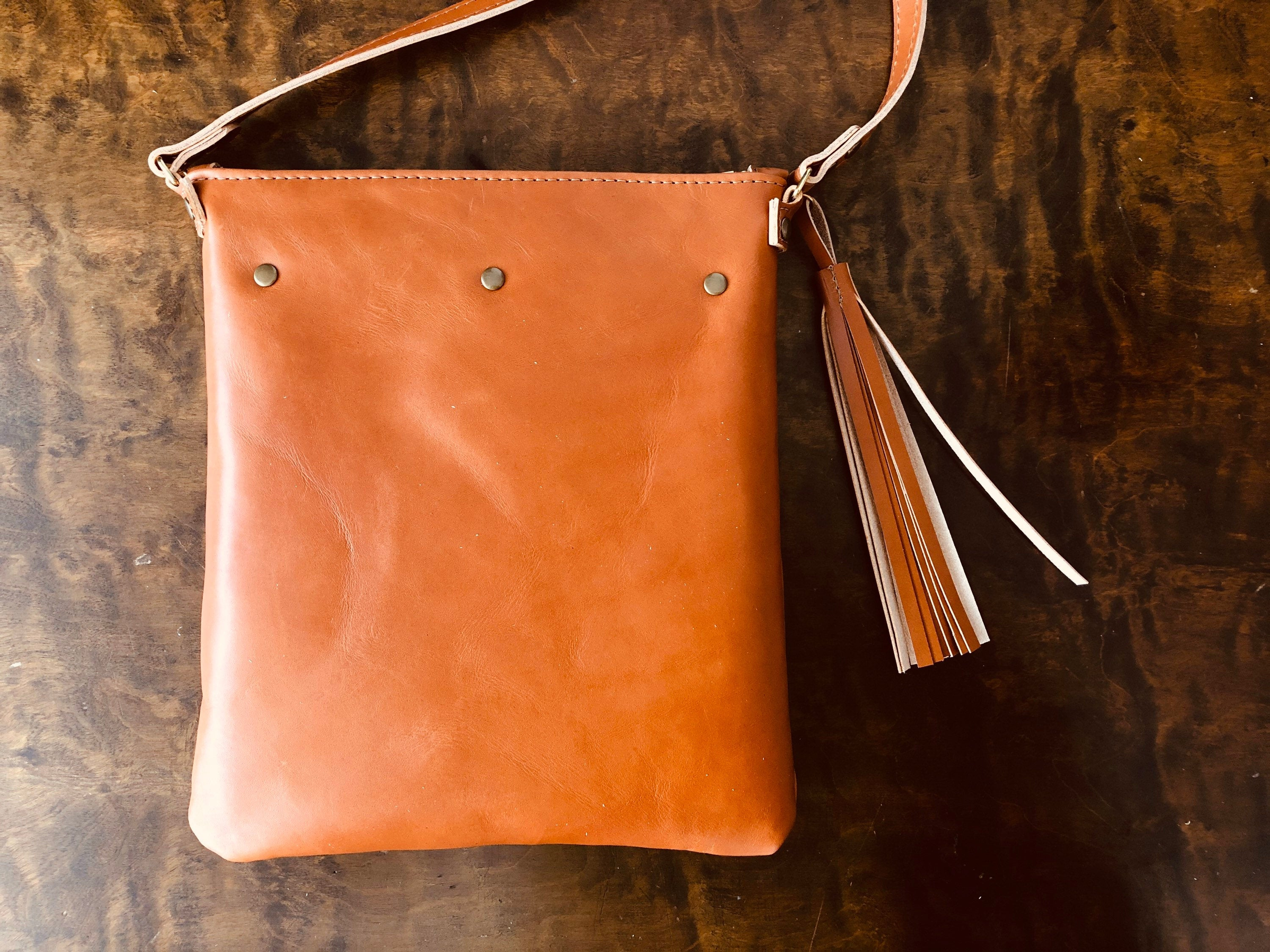 Back of tan crossbody pouch with tassel and three rivets rests on table