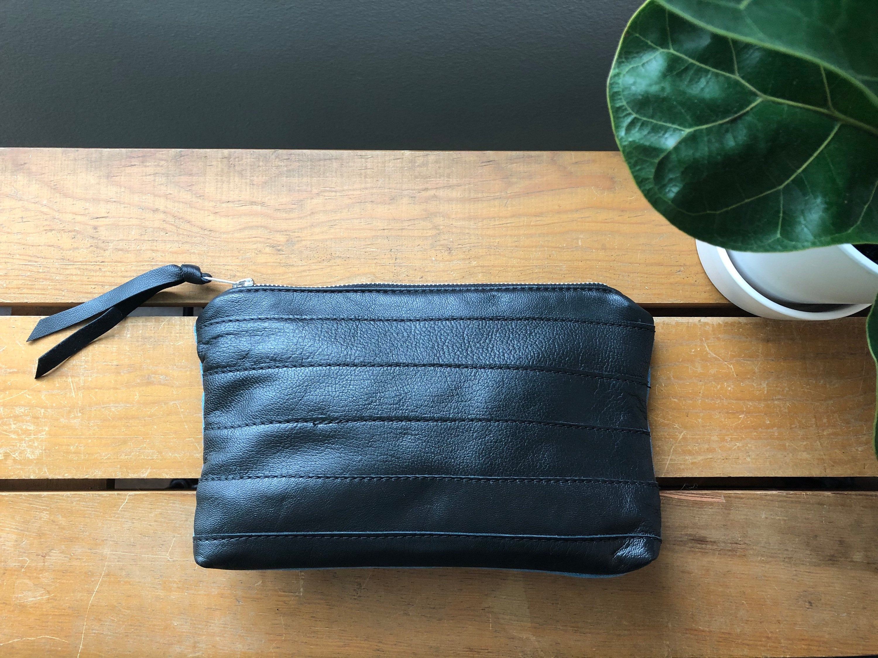 Black leather front of two toned clutch on table near plant