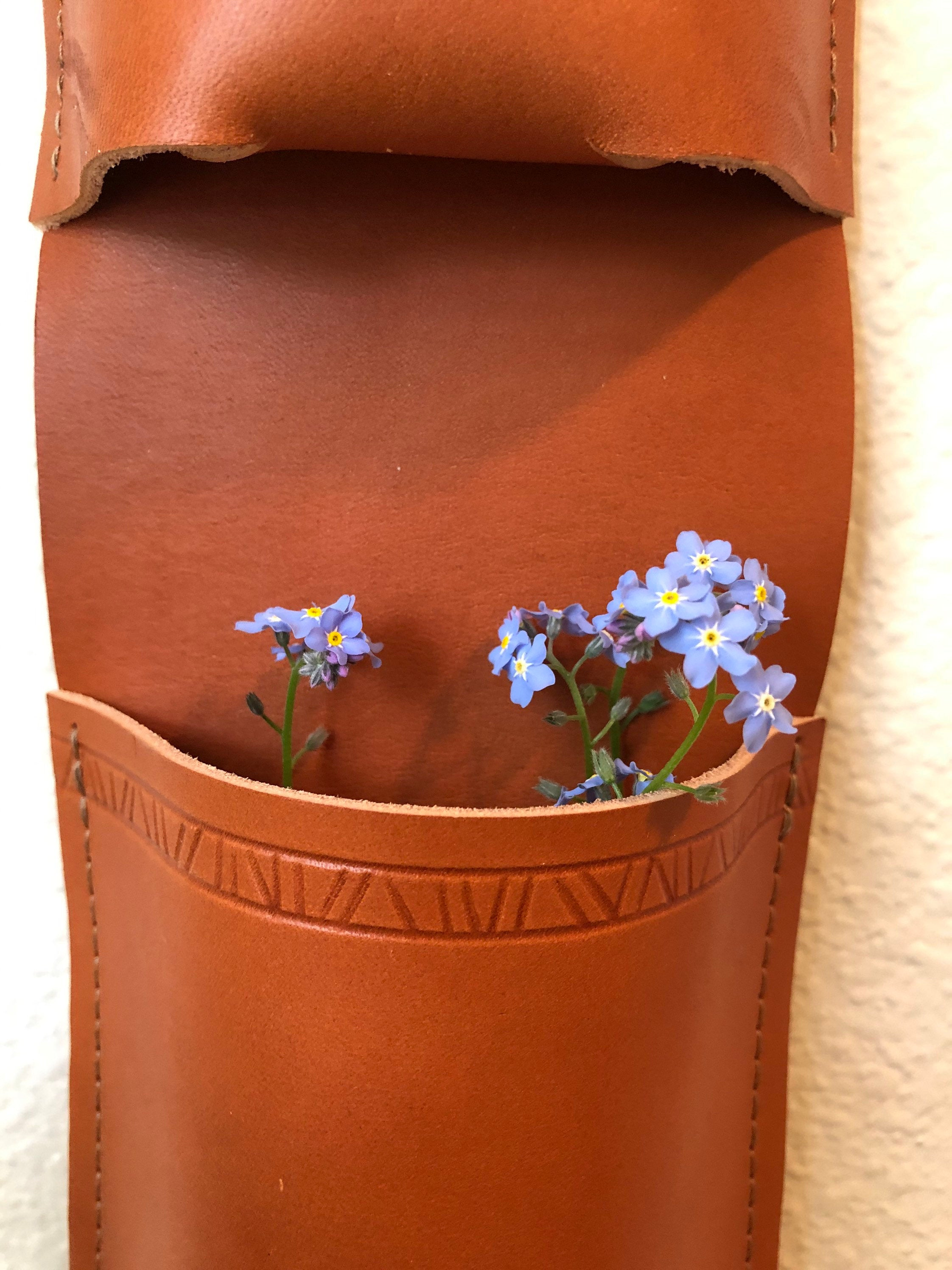 Close up of hanging tan leather organizer with patterned border holds blue forget-me-nots