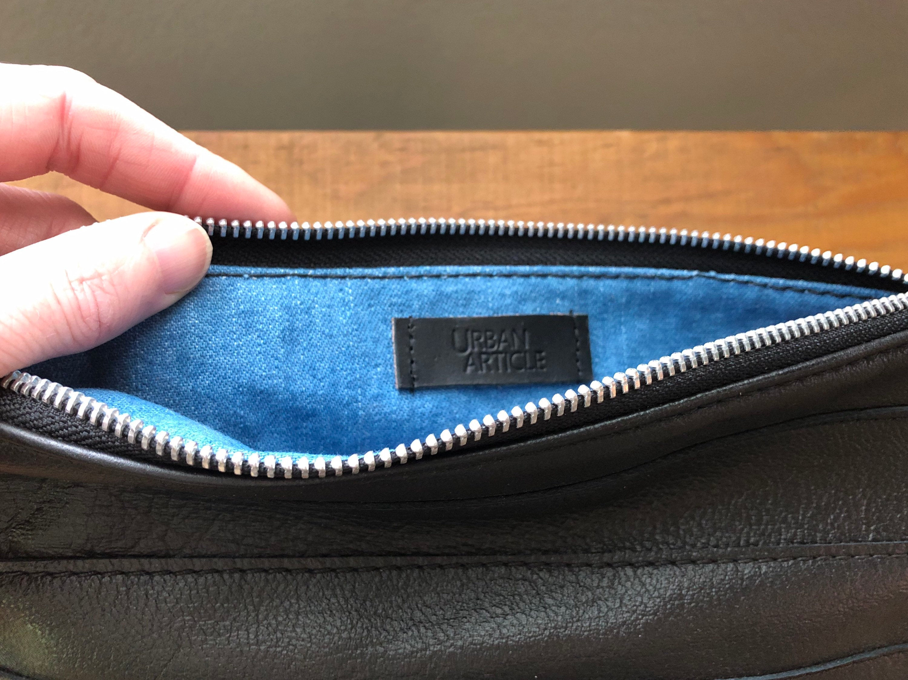 Blue denim interior of black leather and denim clutch, showing Urban Article tag