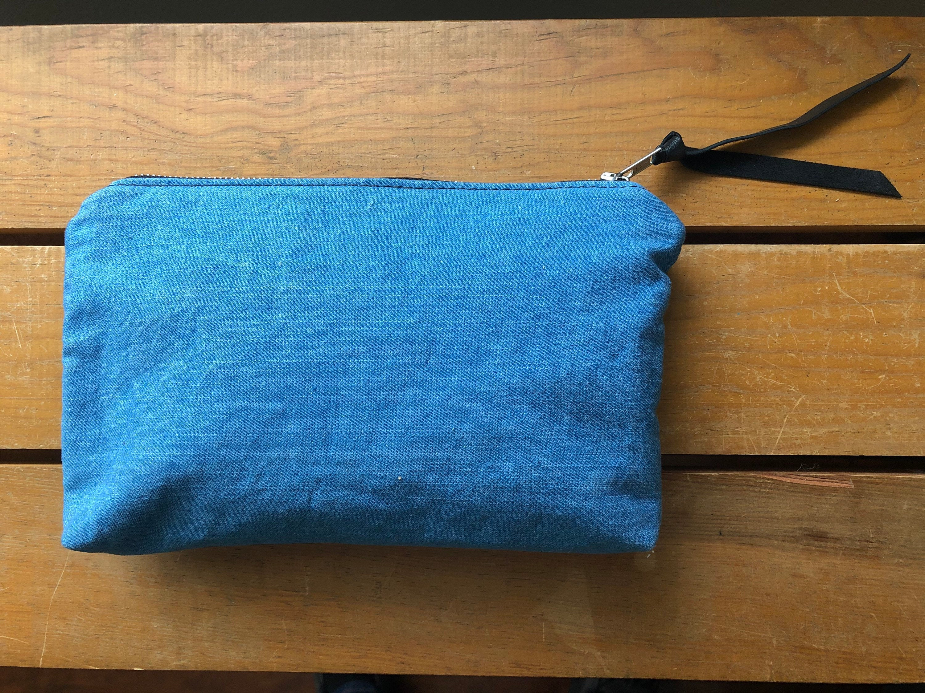 Blue denim clutch back and black leather pull resting on table