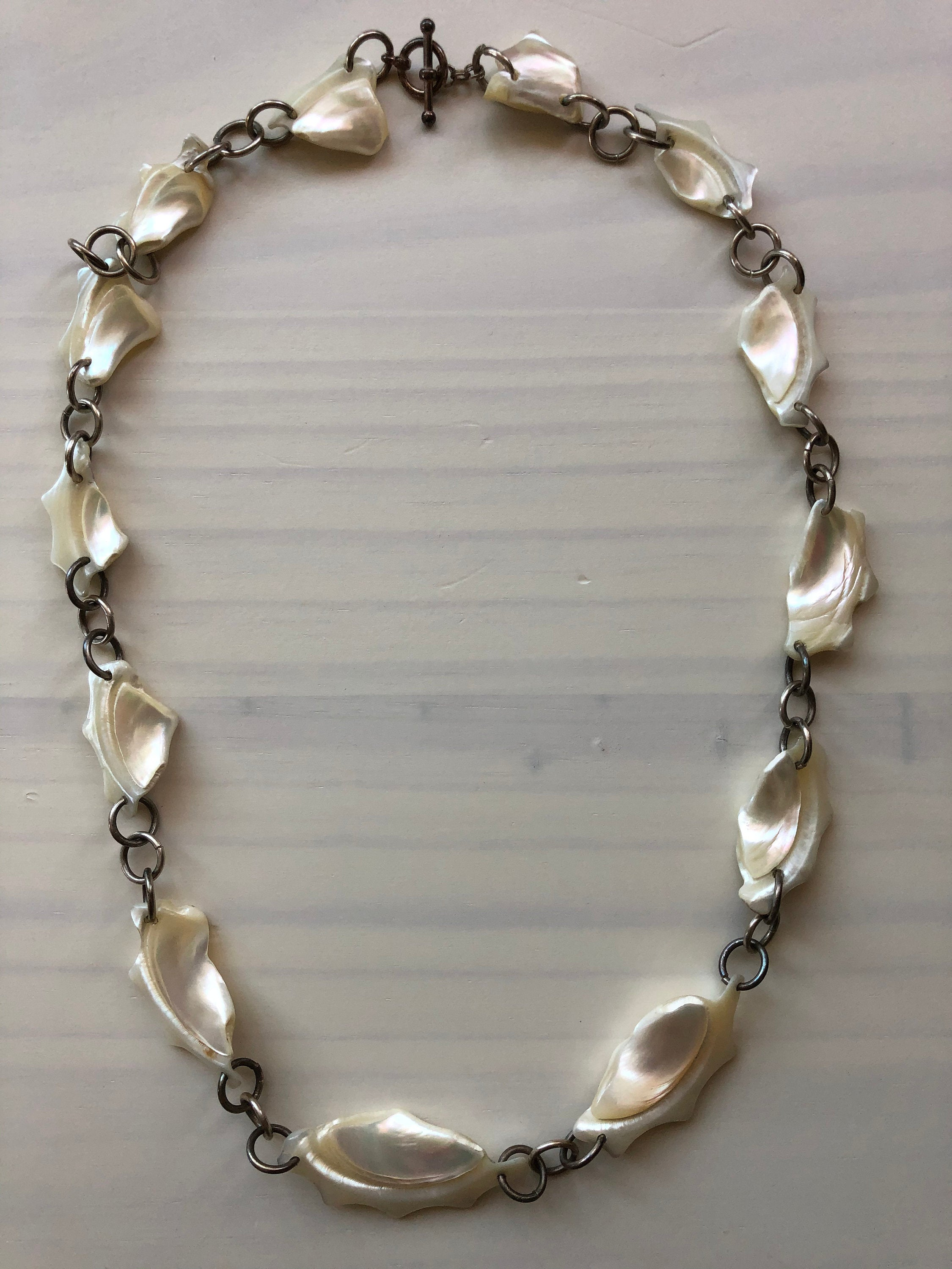 Chunky shell and silver chain necklace on pale wood background