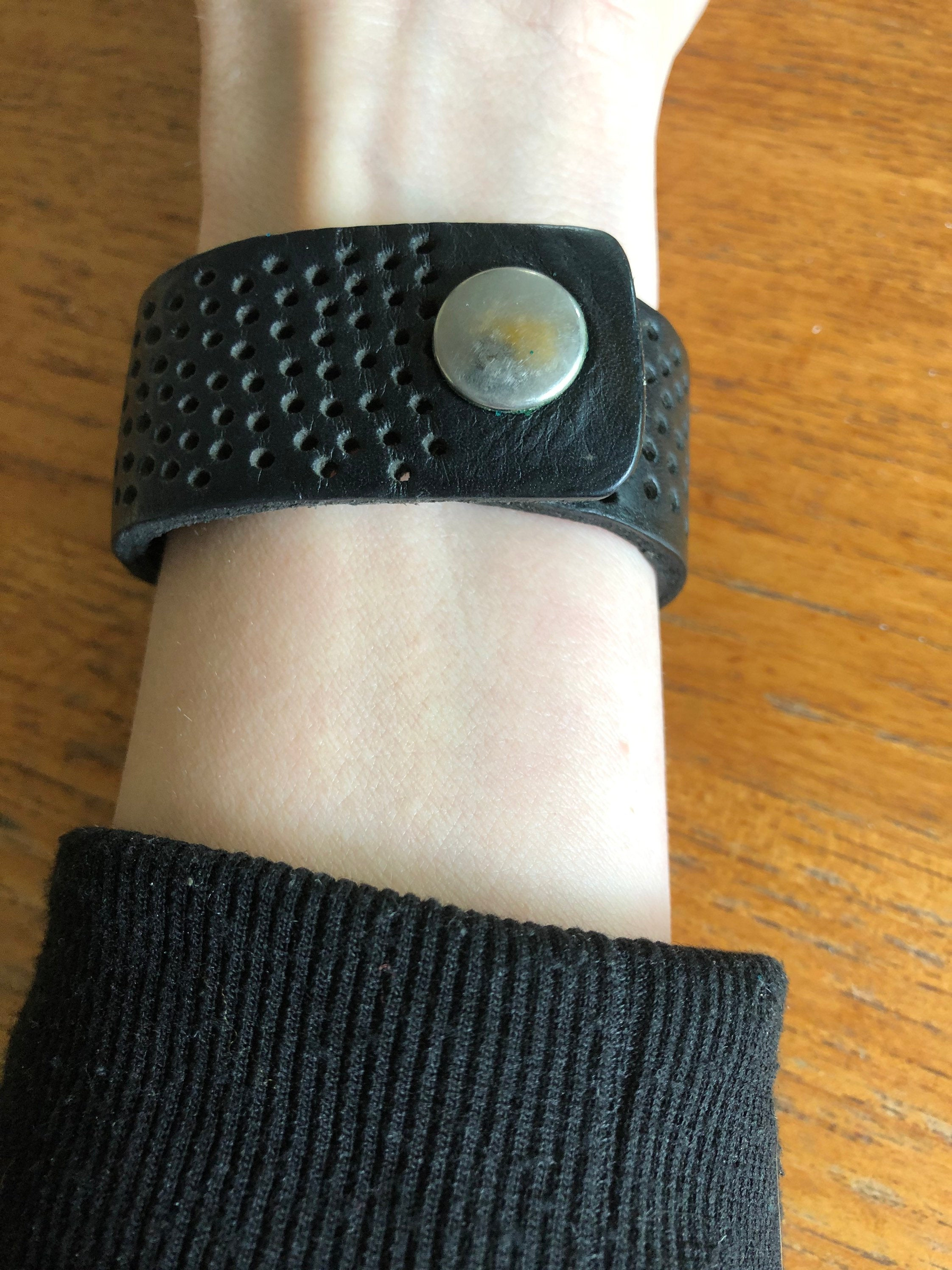 Black leather bracelet with perforated design and snap closure on model's arm with long sleeve