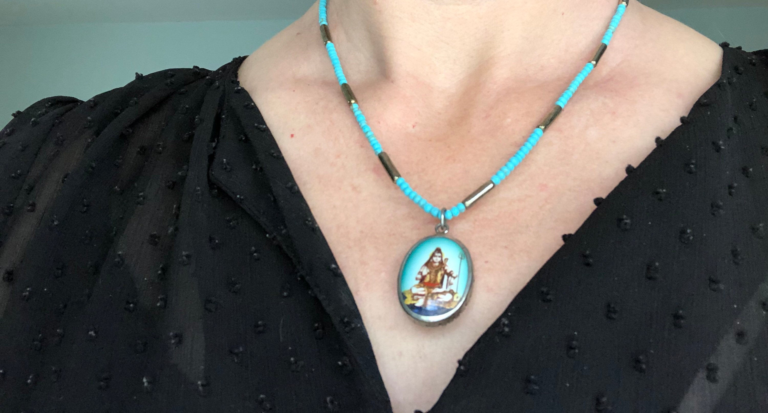 Turquoise and silver beaded necklace with oval deity charm, worn by model in black shirt.