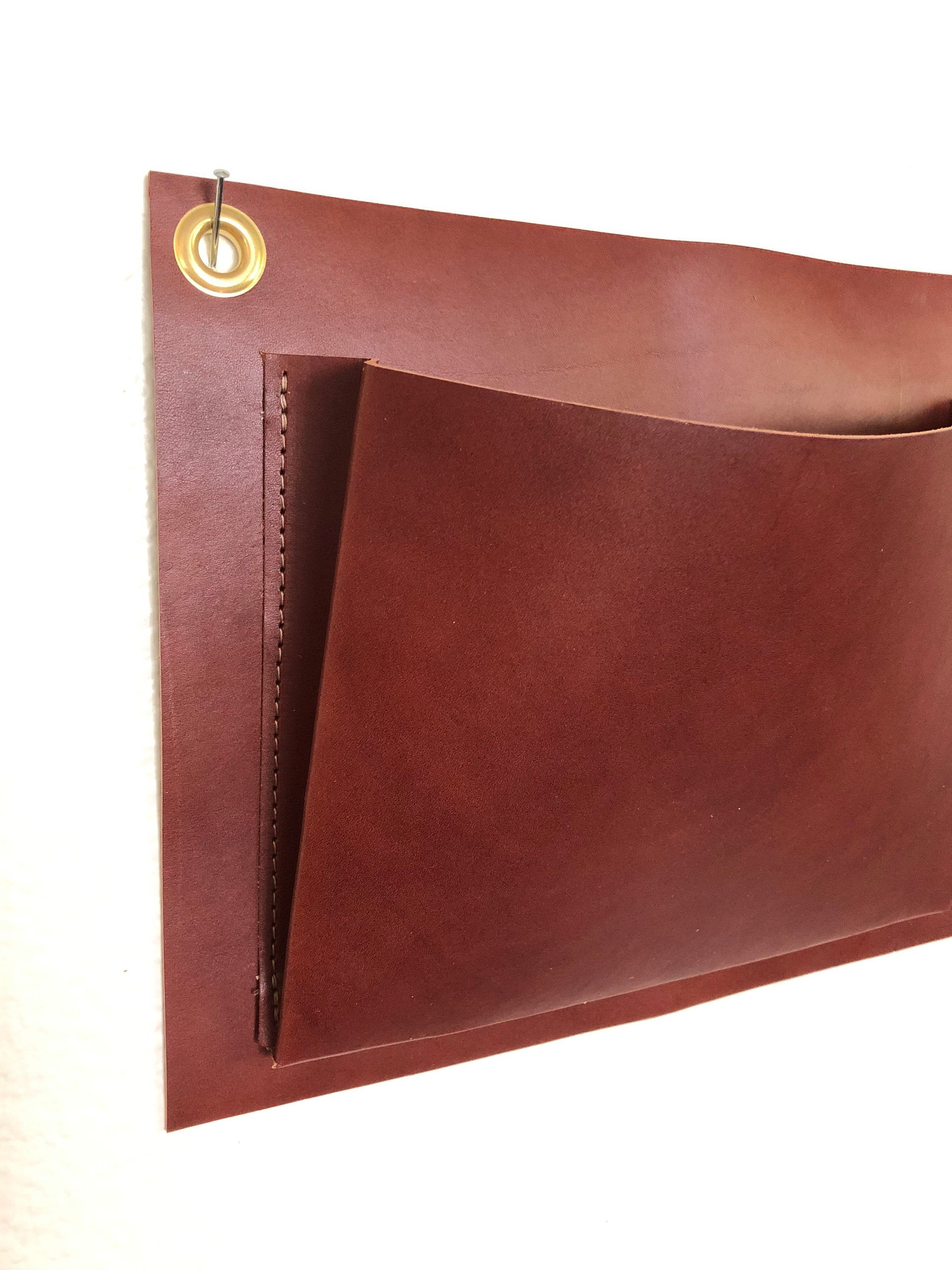 Brown leather wall pocket with brass grommet