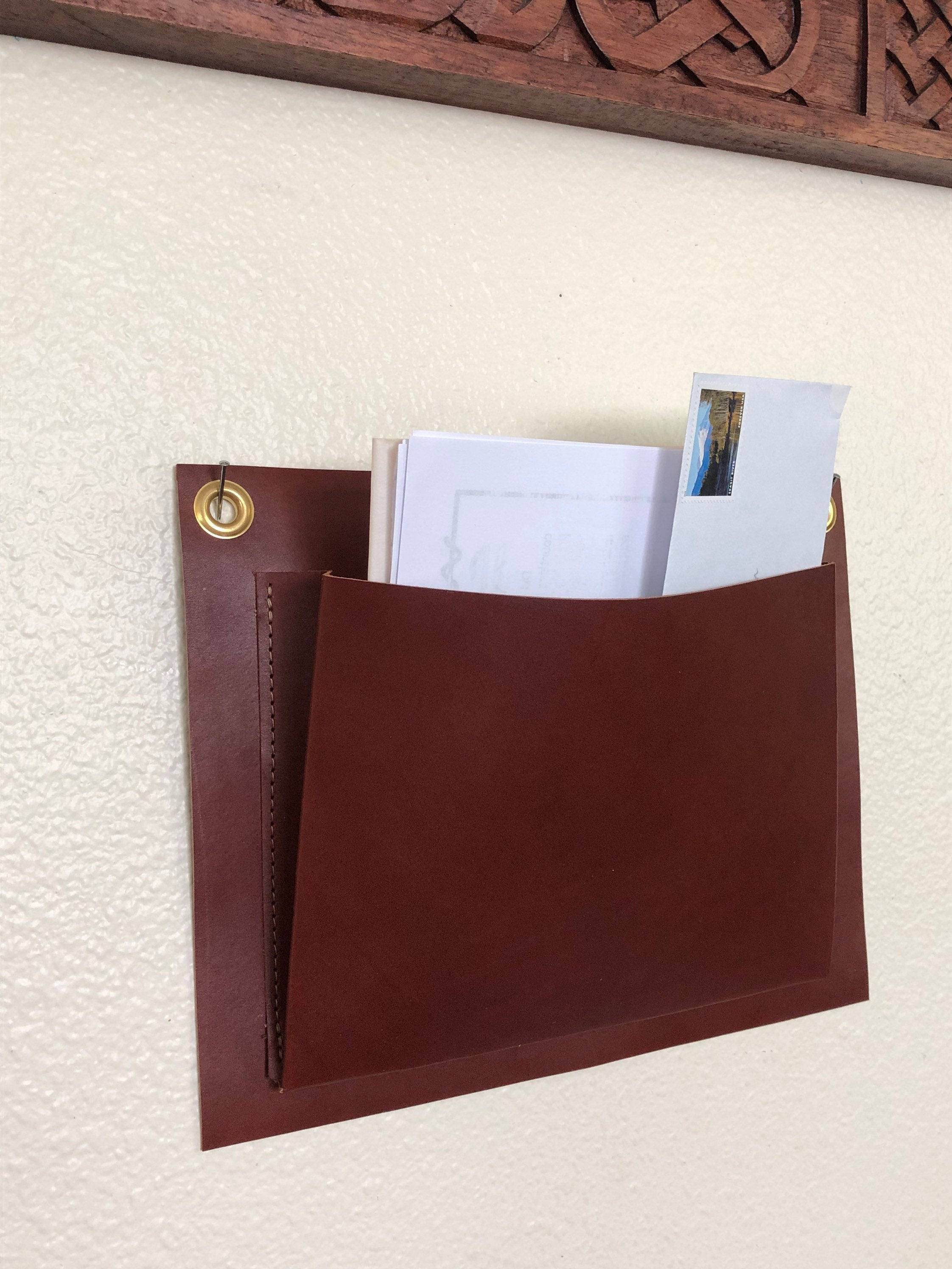 Brown leather wall organizer holds mail and hangs under mirror
