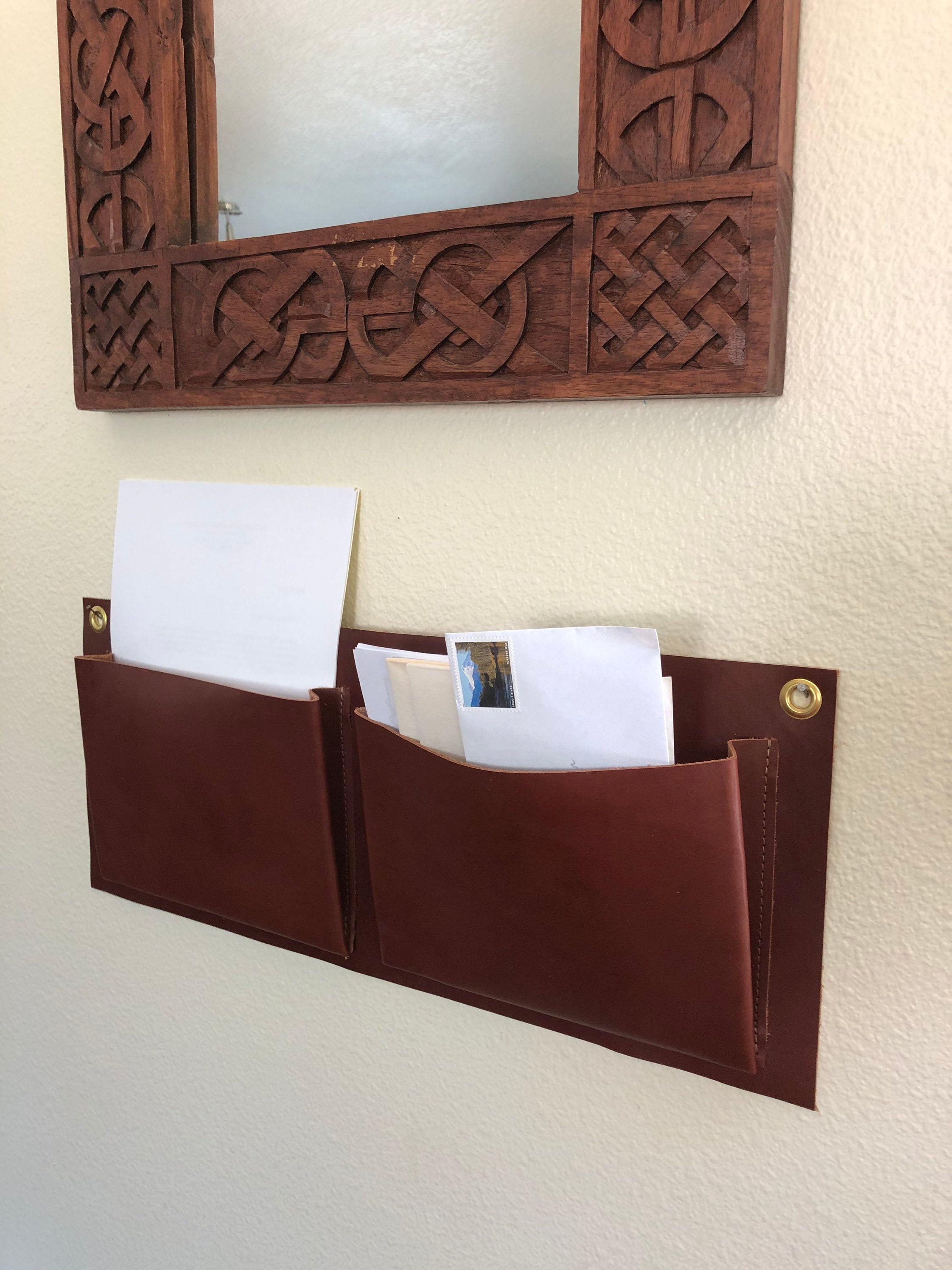 Brown leather wall organizer, two pocket, hangs under mirror holding paperwork