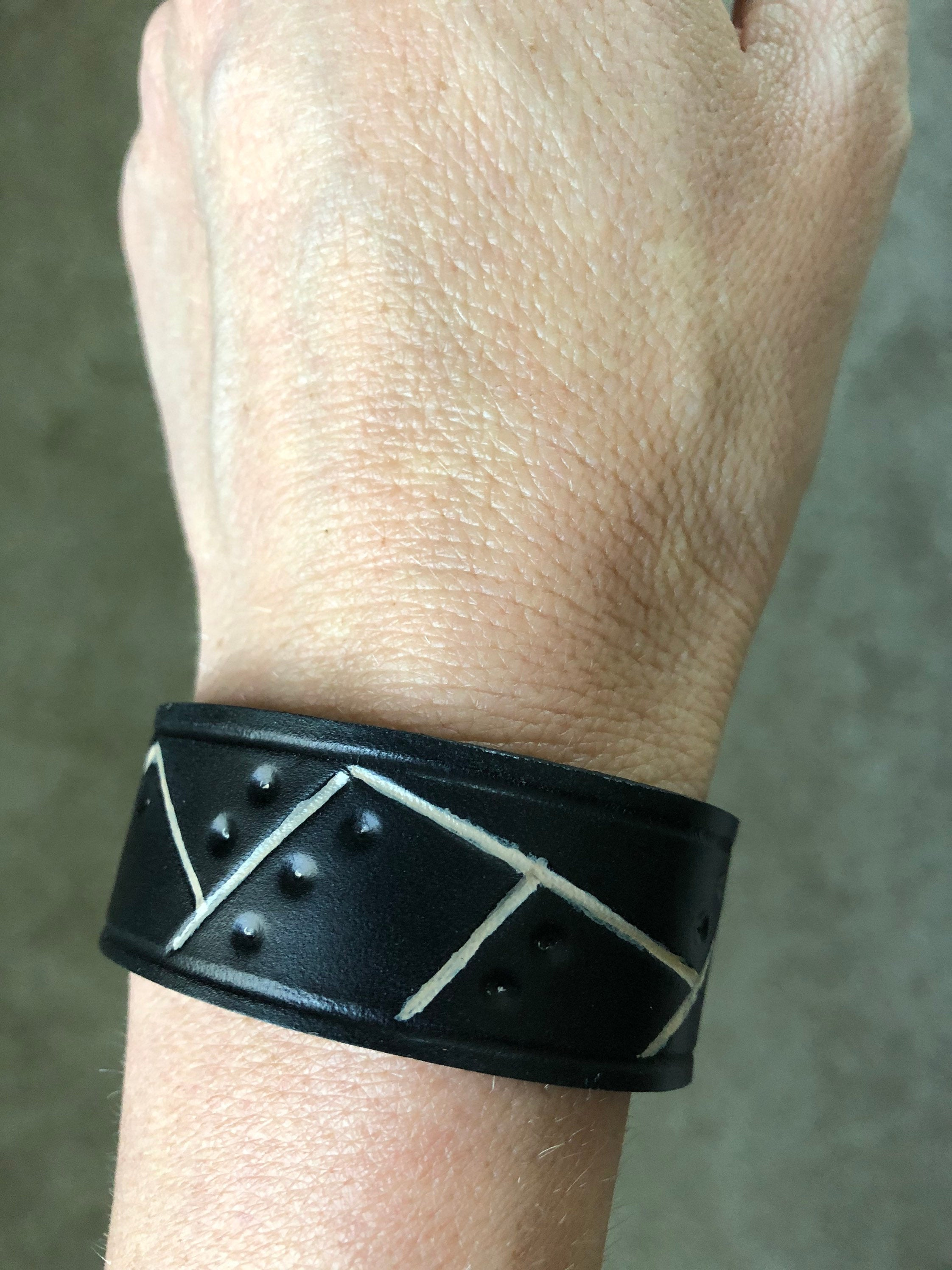 Black leather cuff with tooled design and cream design shown on wrist