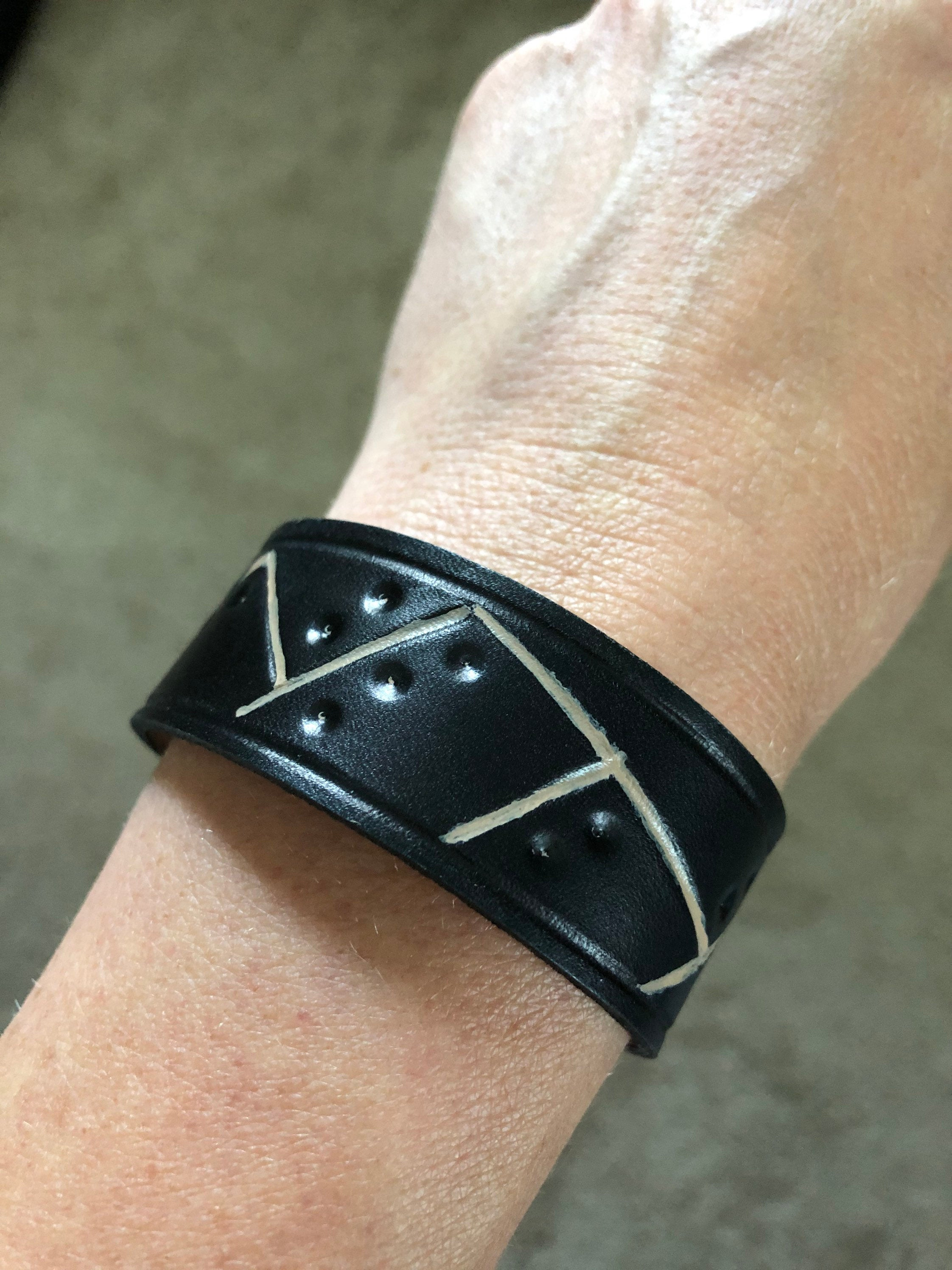 Black leather bracelet with hand painted and tooled detail shown on model's wrist