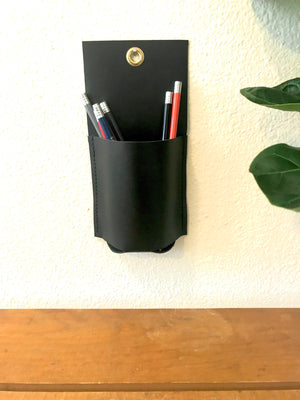 Open image in slideshow, Small black leather wall caddy holds colored pencils above a wooden table