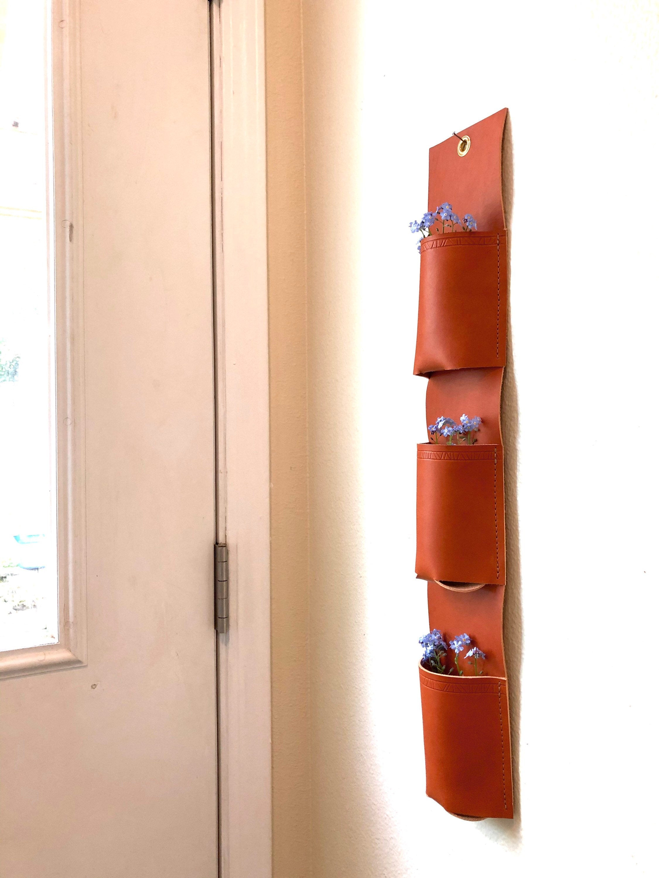 Tan leather vertical organizer with three pockets holds blue forget-me-nots by windowed door