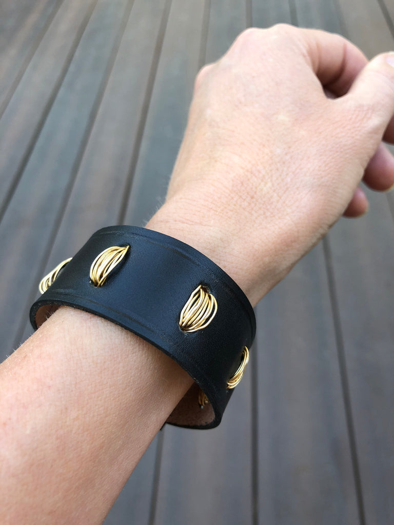 Black and gold leather bracelet on model's arm.