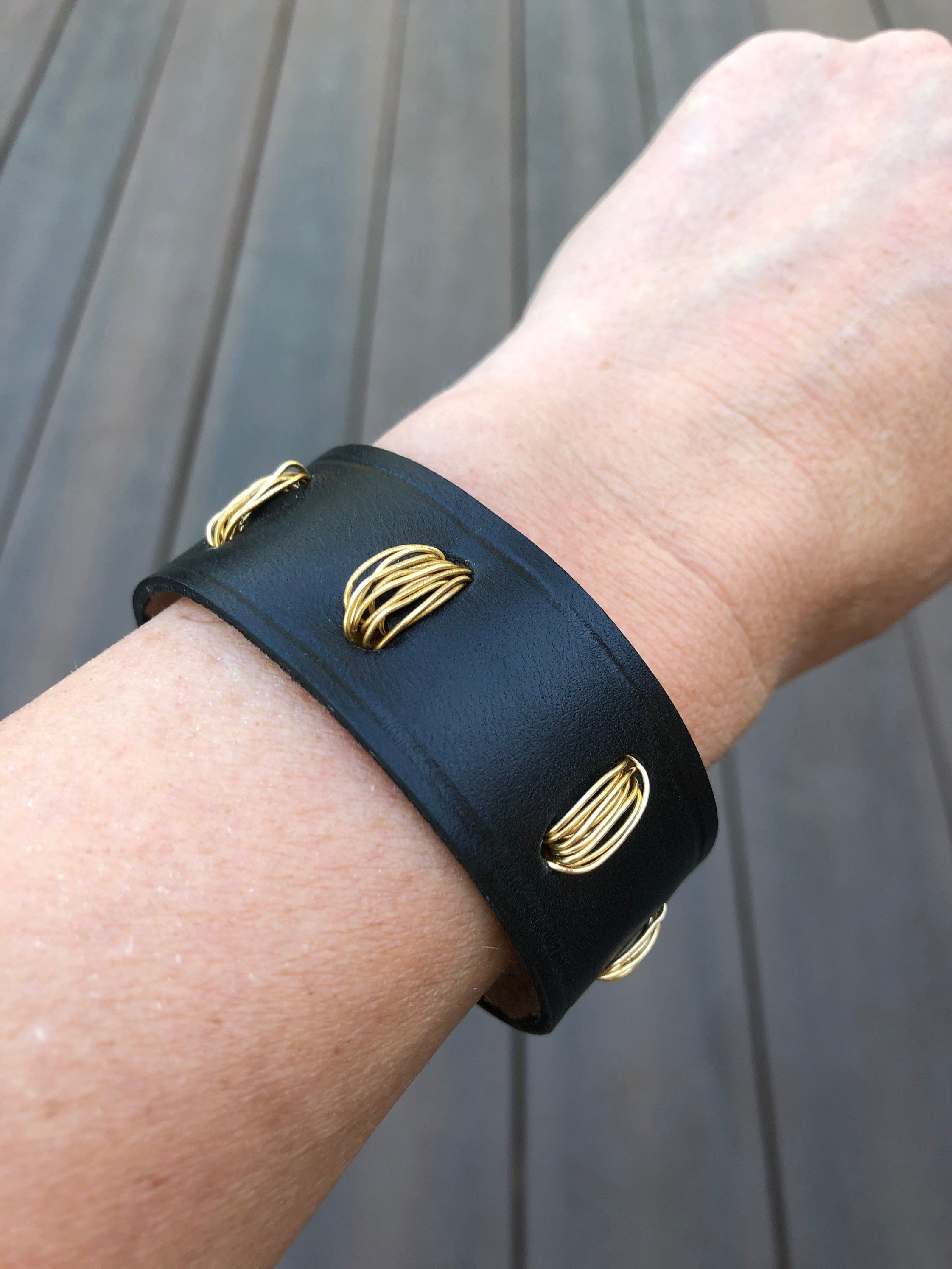 Black leather bracelet with gold wire detail, shown on wrist