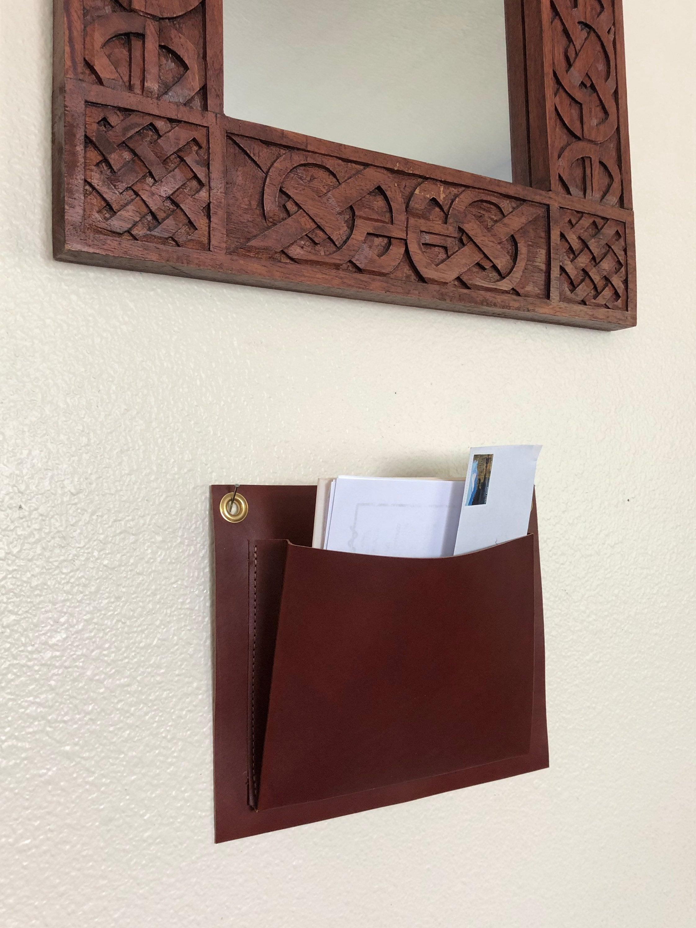 Brown leather wall organizer hangs under mirror and holds mail