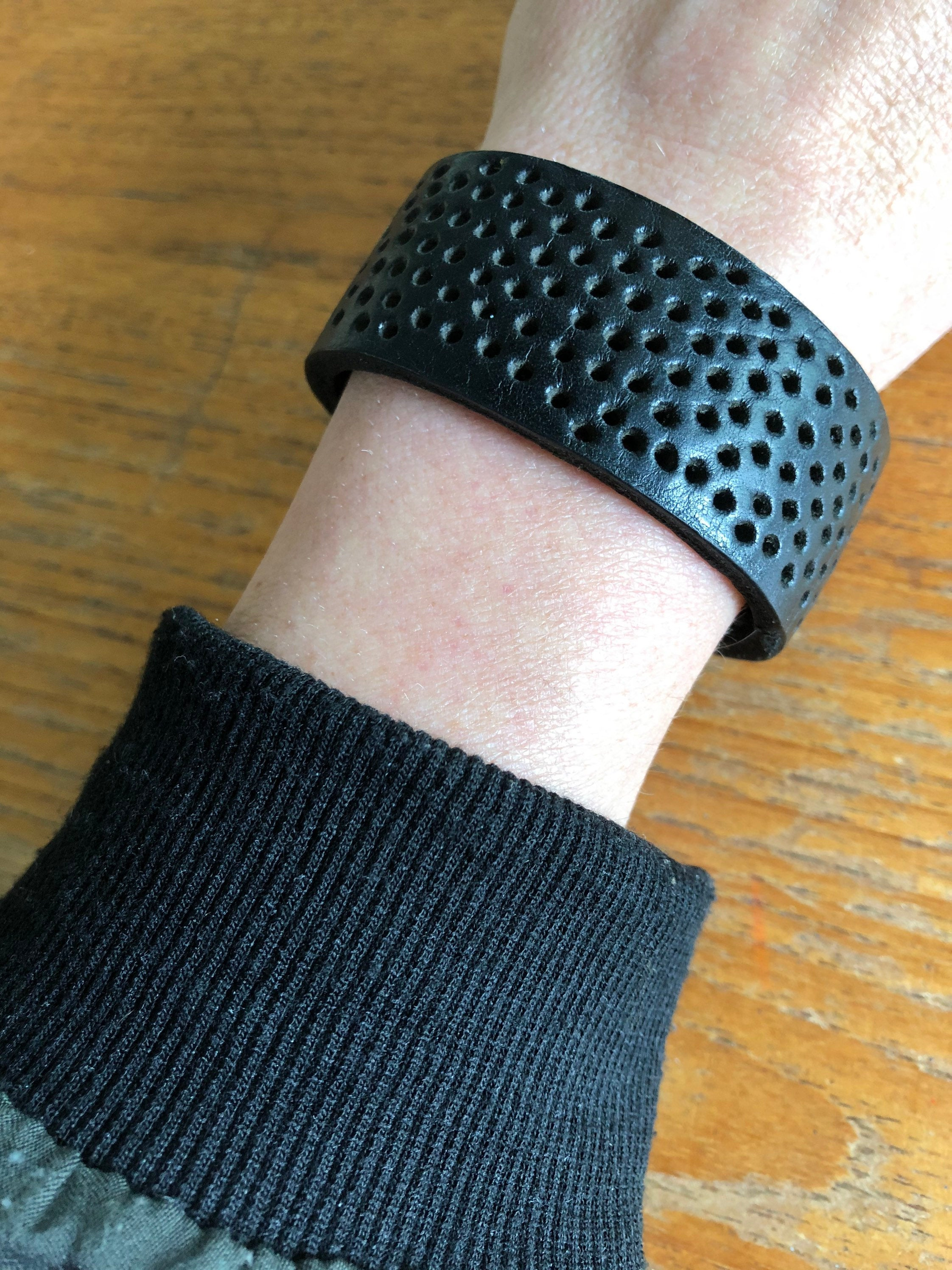 Black leather cuff bracelet with perforated detail worn by model with black and green sleeve