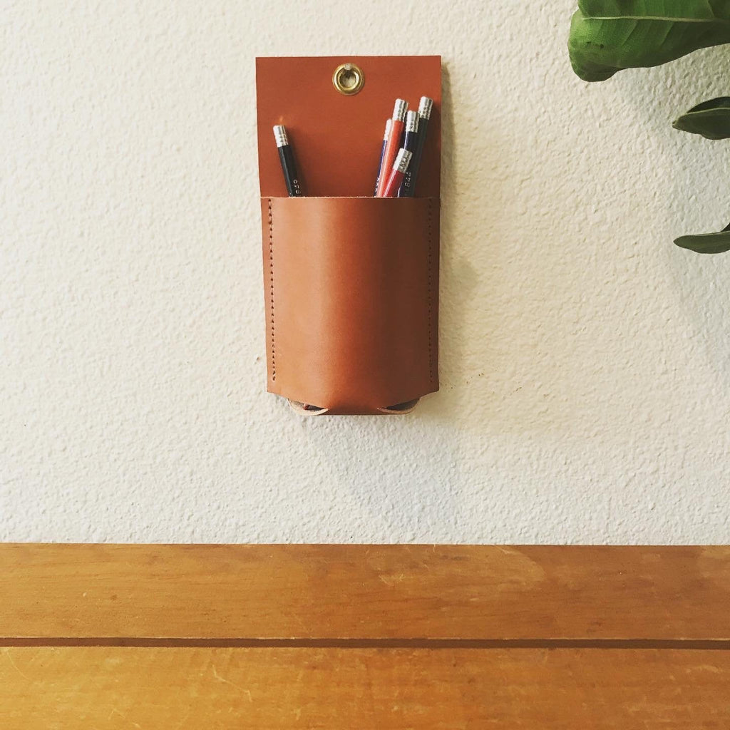 Tan leather wall organizer hangs holding colored pencils above a wood table