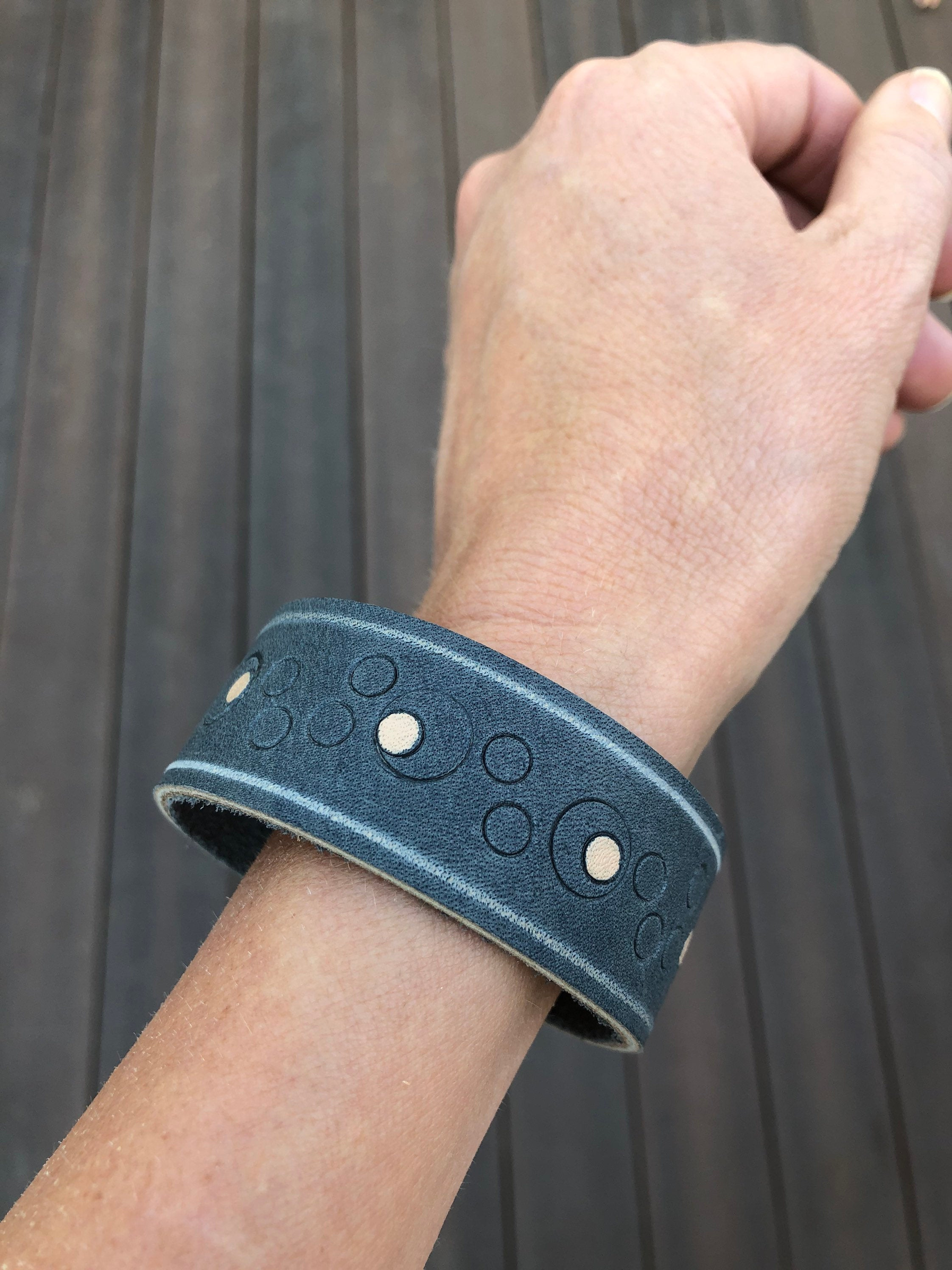 Blue leather cuff bracelet with circular pattern detail shown on model's wrist