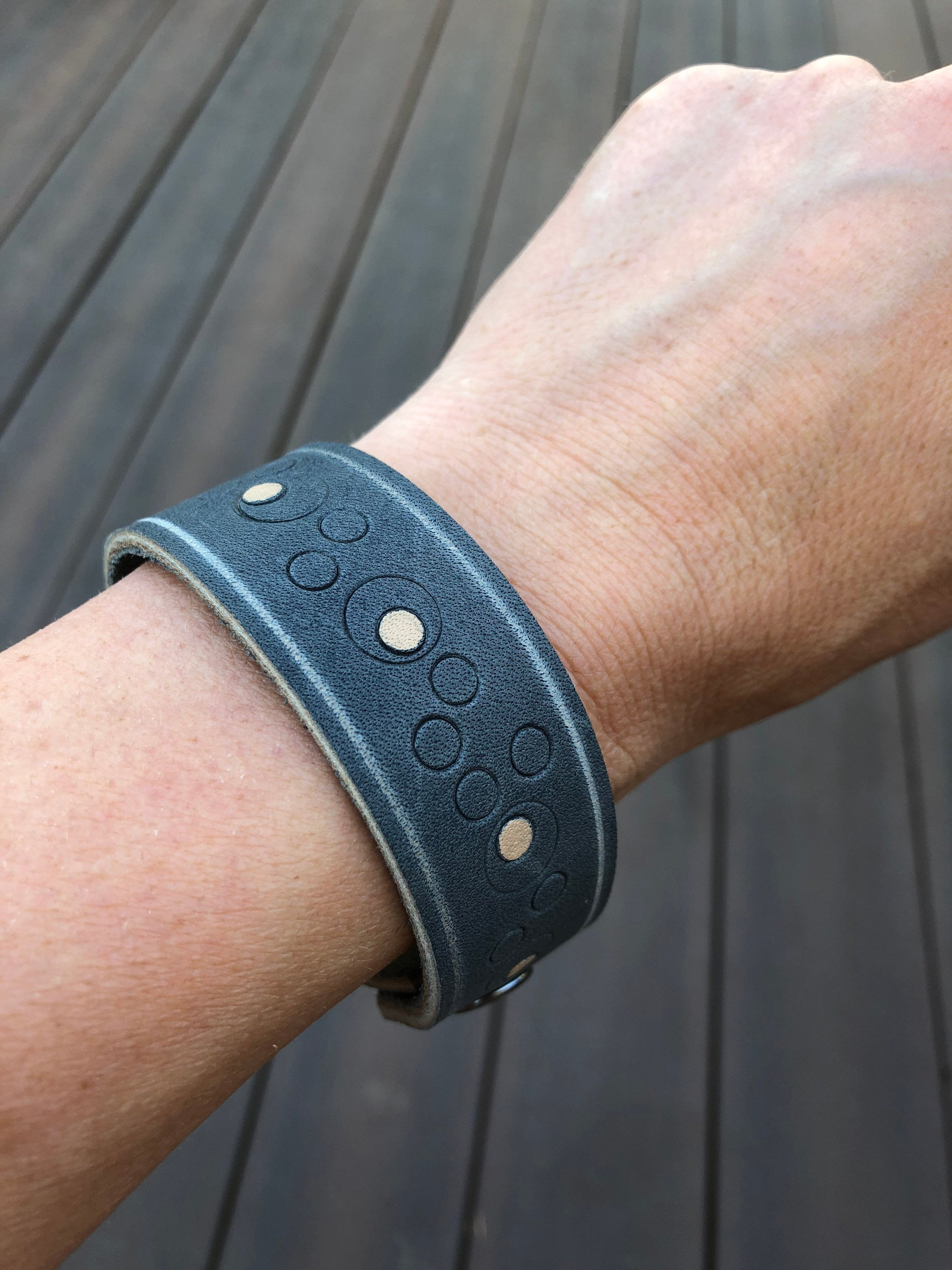 Blue leather cuff bracelet with pattern detail shown on model's wrist