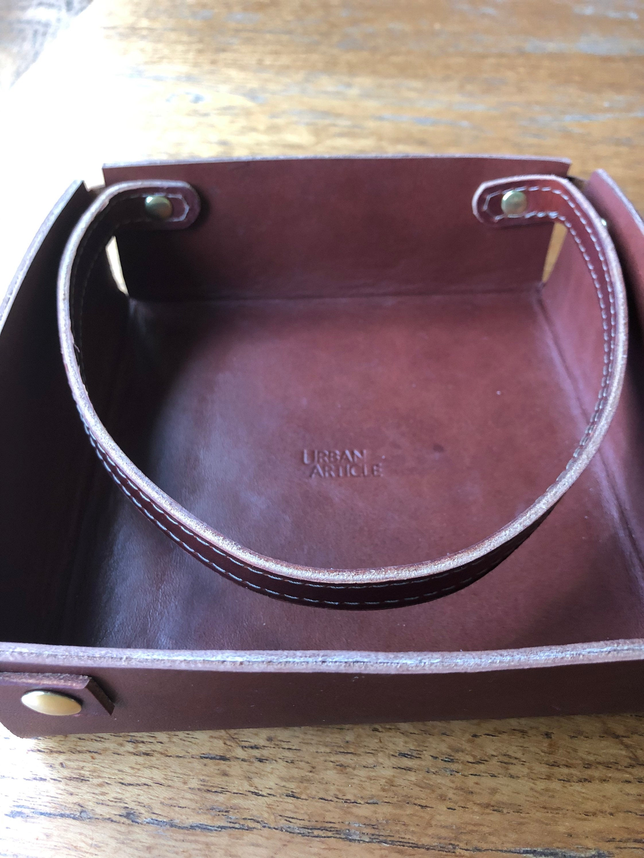 Brown leather napkin holder with strap keeper rests on wooden table