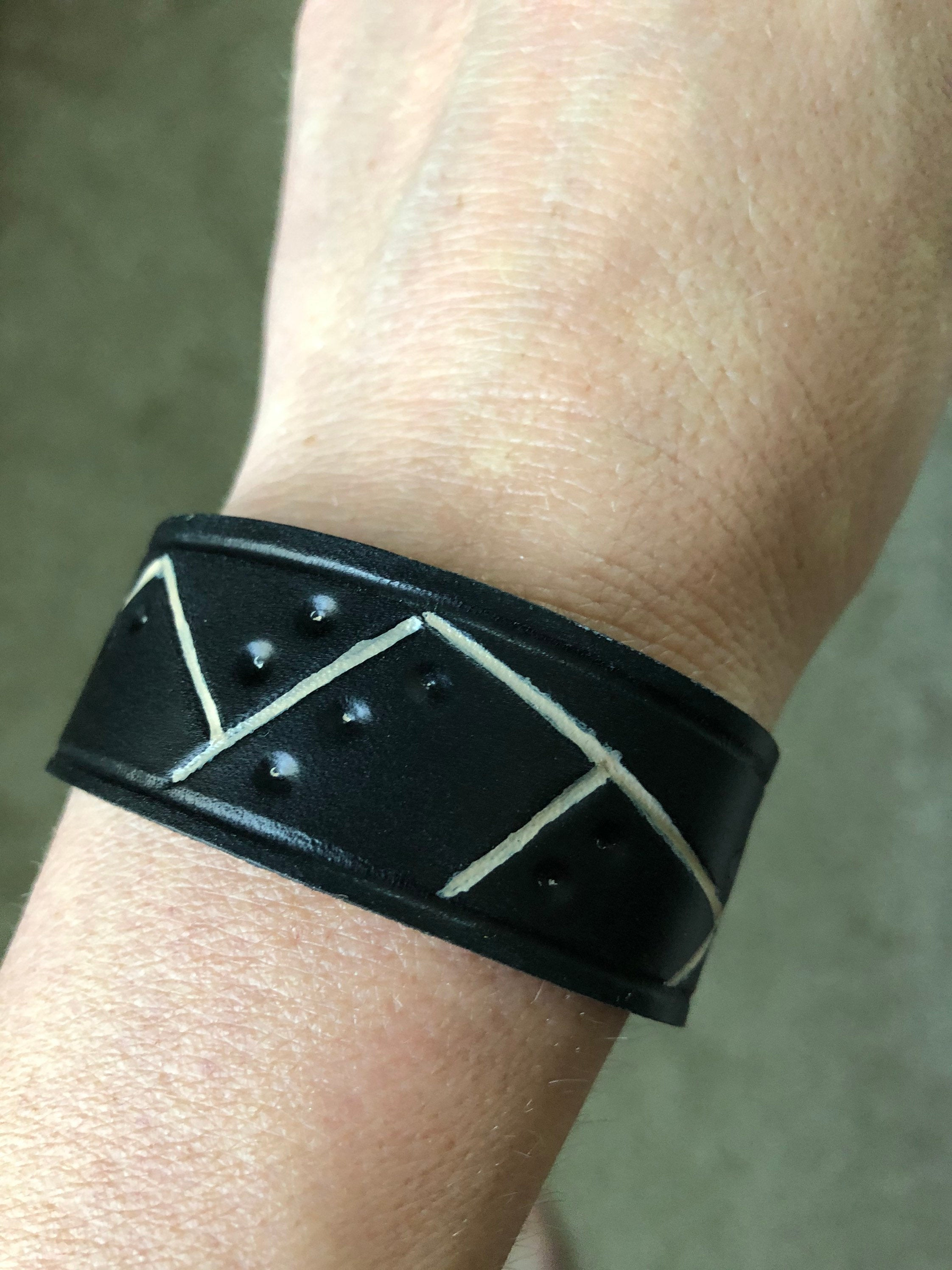 Black leather cuff bracelet with tan painted lines and circular embossed detail shown on wrist