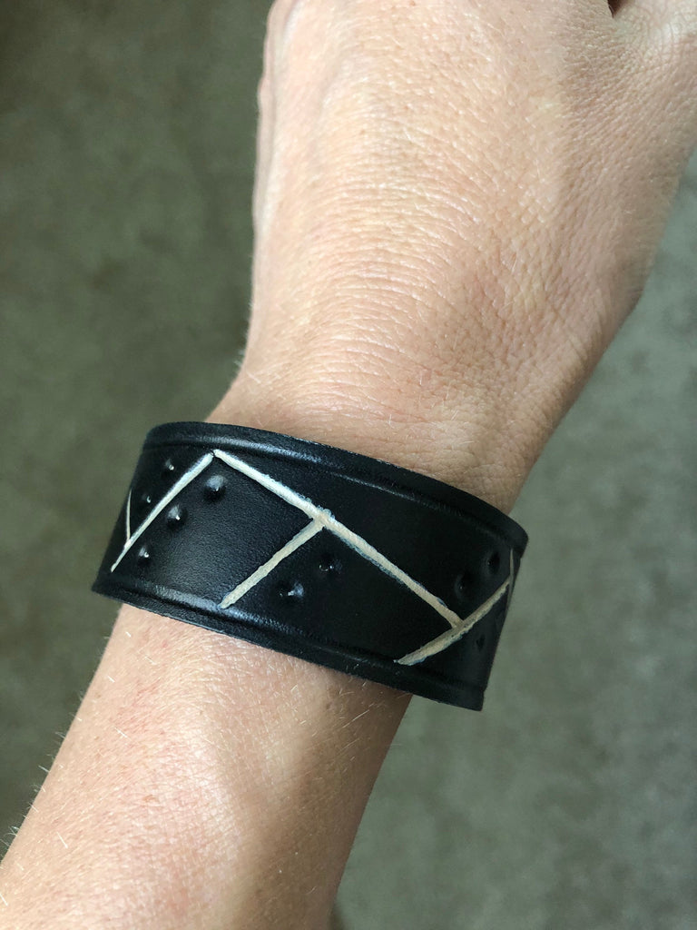 Black leather cuff bracelet with cream painted and embossed detail shown on wrist