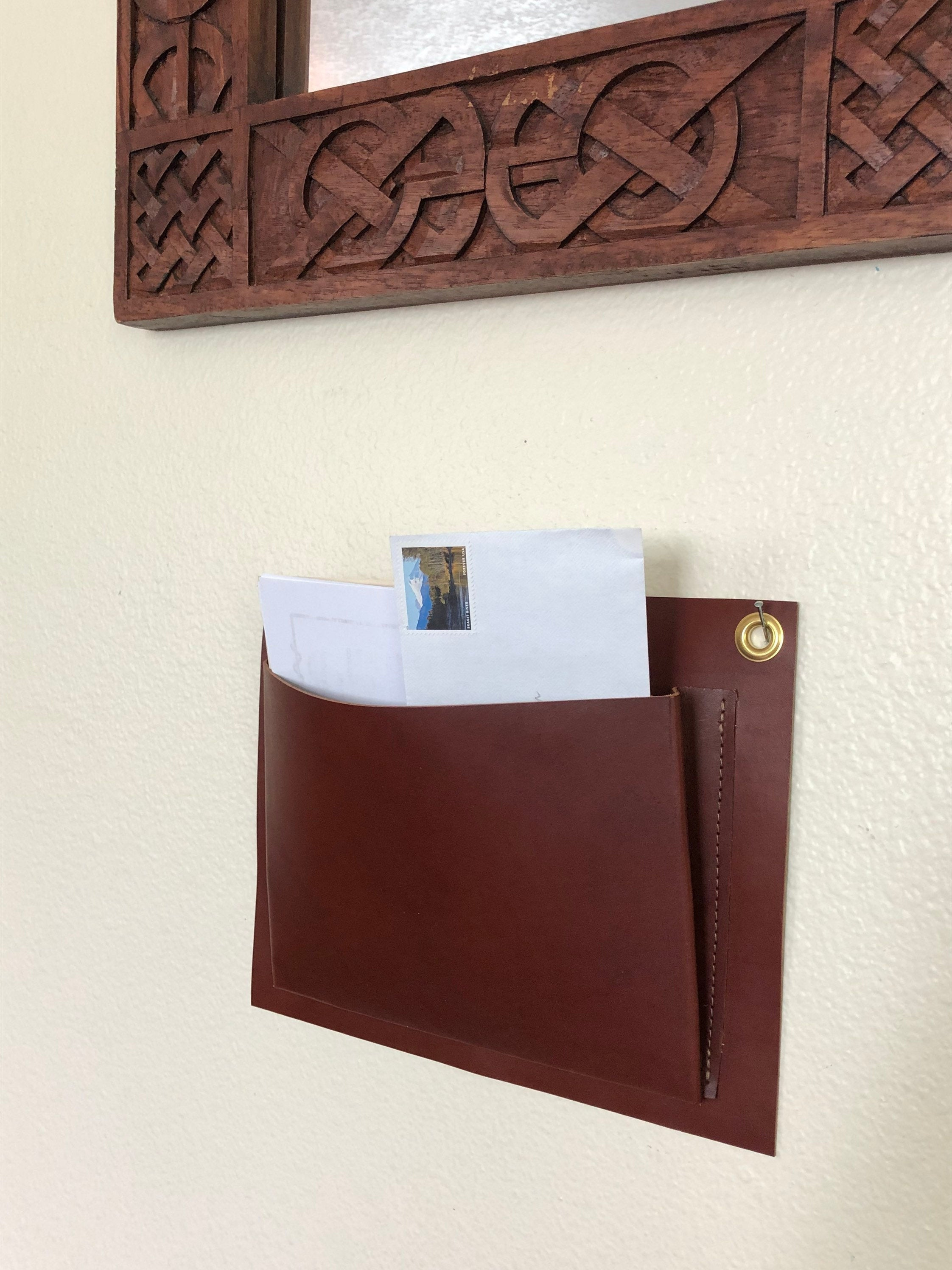 Brown leather wall organizer hangs under mirror