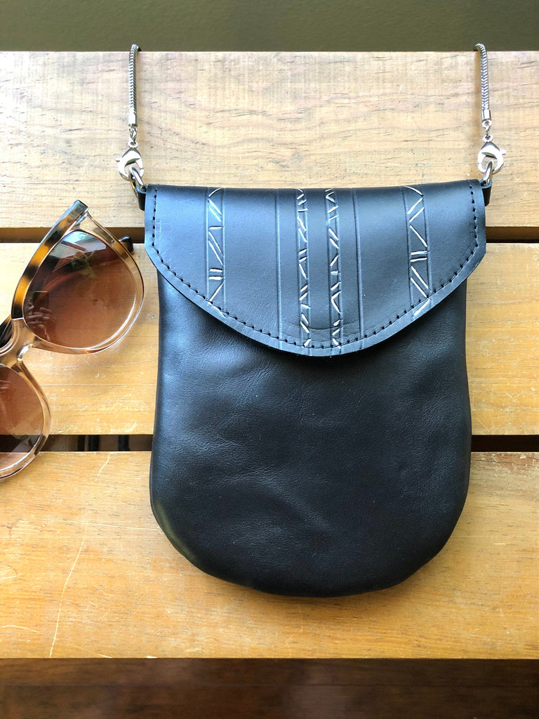Small black painted crossbody pouch rests on table near sunglasses