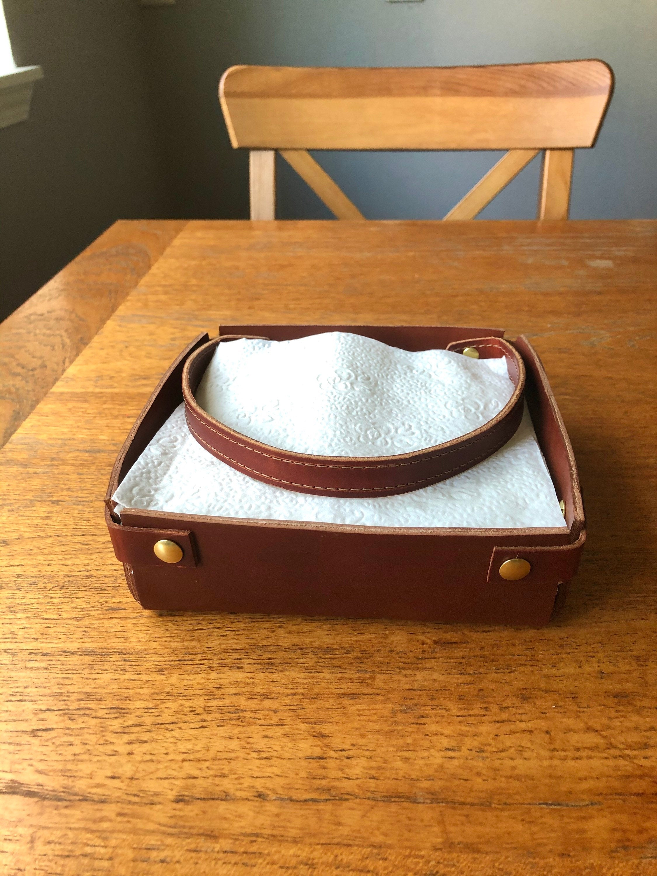 Brown leather napkin holder with brass details sits on kitchen table