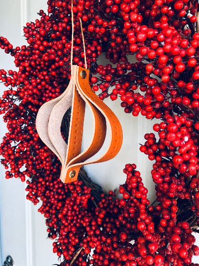 Leather ornament hangs on red wreath.
