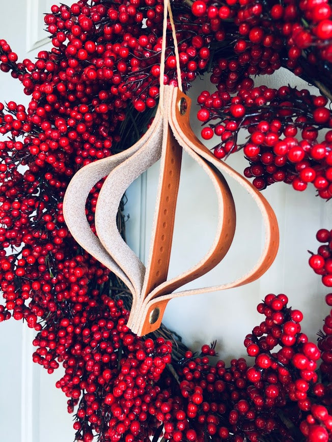 Leather Christmas ornament hangs on red wreath.