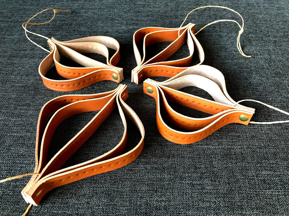 Four leather ornaments lie in an arrangement.