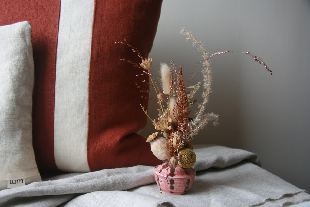 A rust-coloured red squirrel cushion with a small vase of dried flowers in front of it.