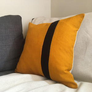 Bee cushion on grey sofa with black stripe
