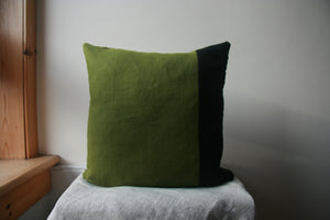 Square cushion cover, of which three quarters is green and one quarter is black.