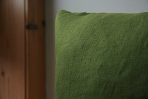 Close up image of corner of cushion. Green fabric visible against background of cream and wood
