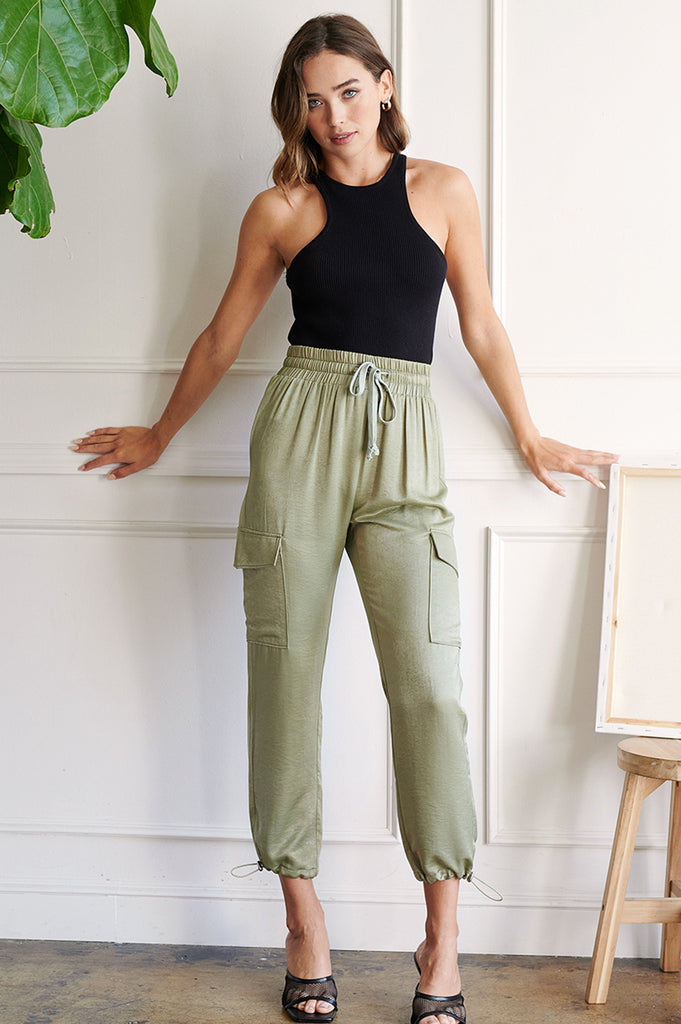 A woman wearing a black rib racer tank top and an olive utility satin jogger pants.