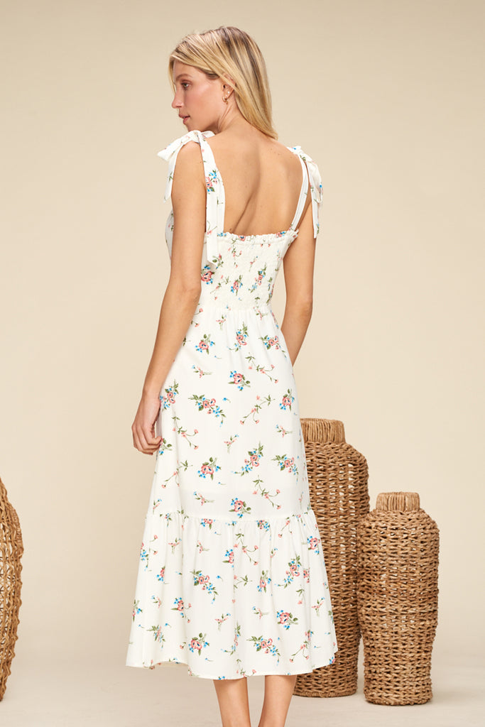 Back side of an ivory sweetheart neckline floral midi dress with shoulder tie fastening.