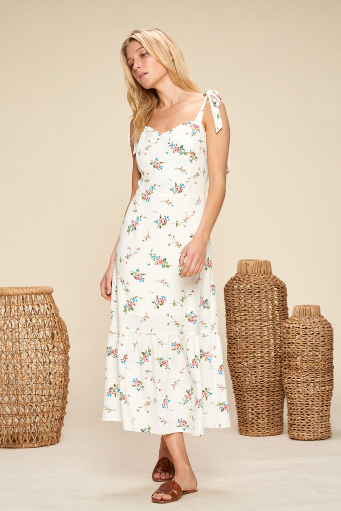 A woman wearing an ivory sweetheart neckline floral midi dress with shoulder tie fastening.