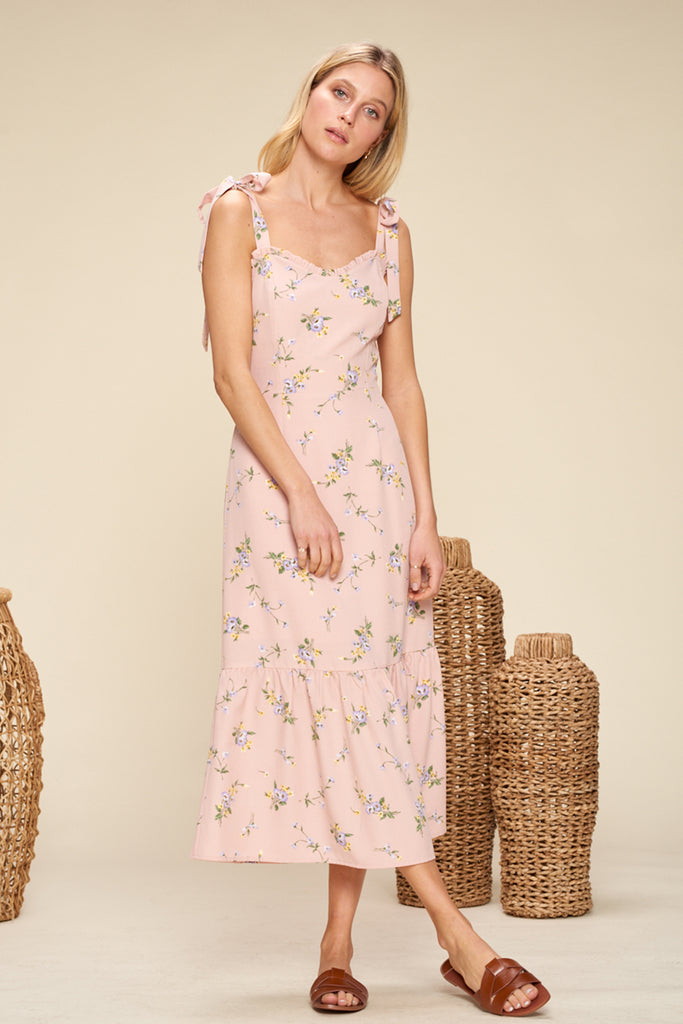 A woman wearing a mauve sweetheart neckline floral midi dress with shoulder tie fastening.