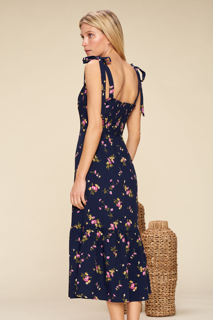 Back side of a navy sweetheart neckline floral midi dress with shoulder tie fastening.