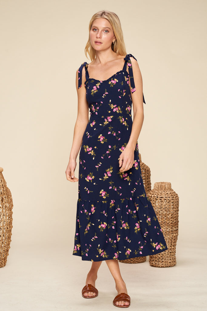 A woman wearing a navy sweetheart neckline floral midi dress with shoulder tie fastening.