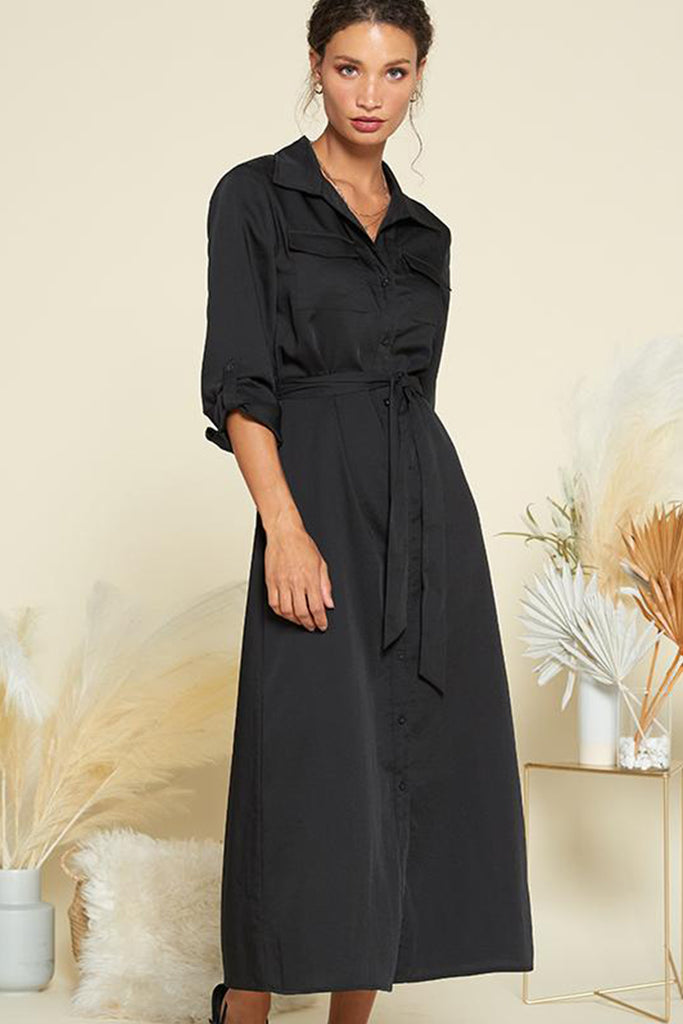A woman wearing a black satin utility shirt midi dress with self waistband included.