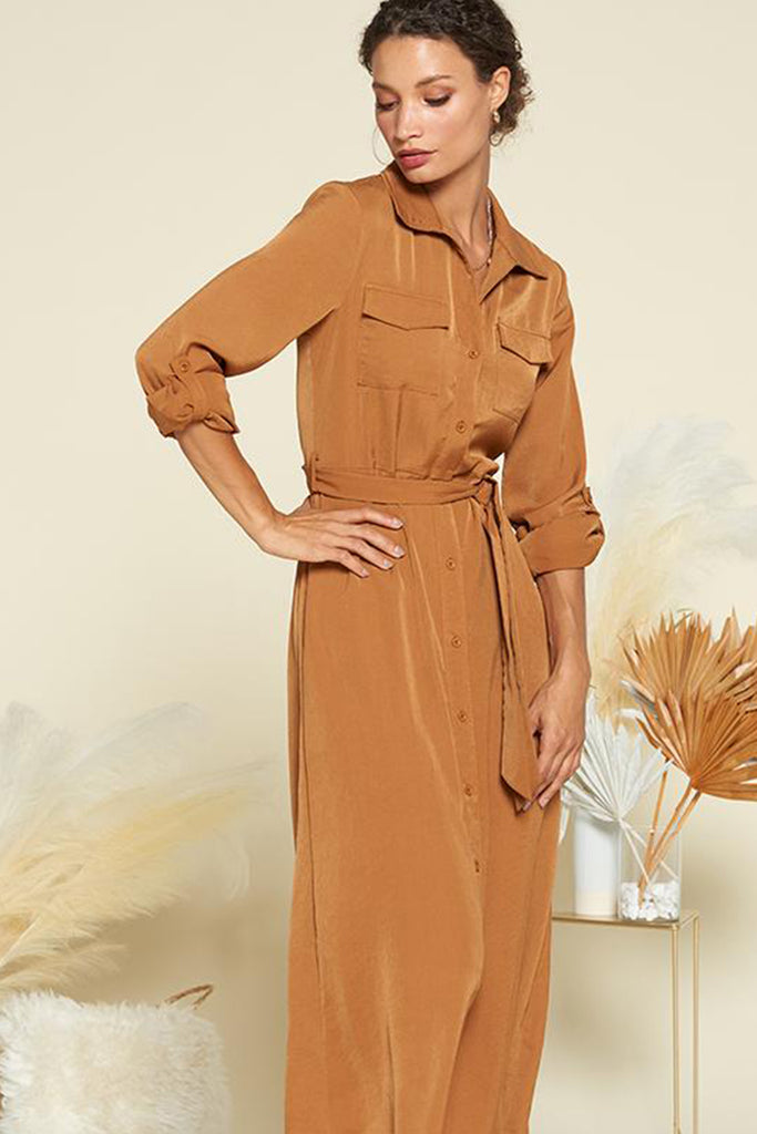 A woman wearing a brown satin utility shirt midi dress with self waistband included.