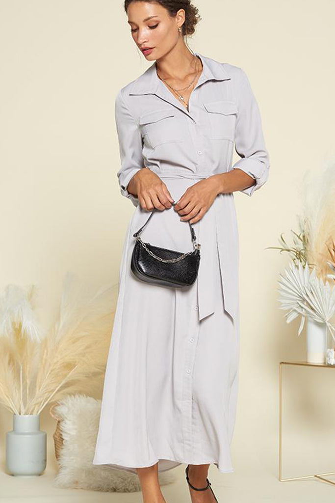 A woman wearing a slate grey satin utility shirt midi dress with self waistband included.