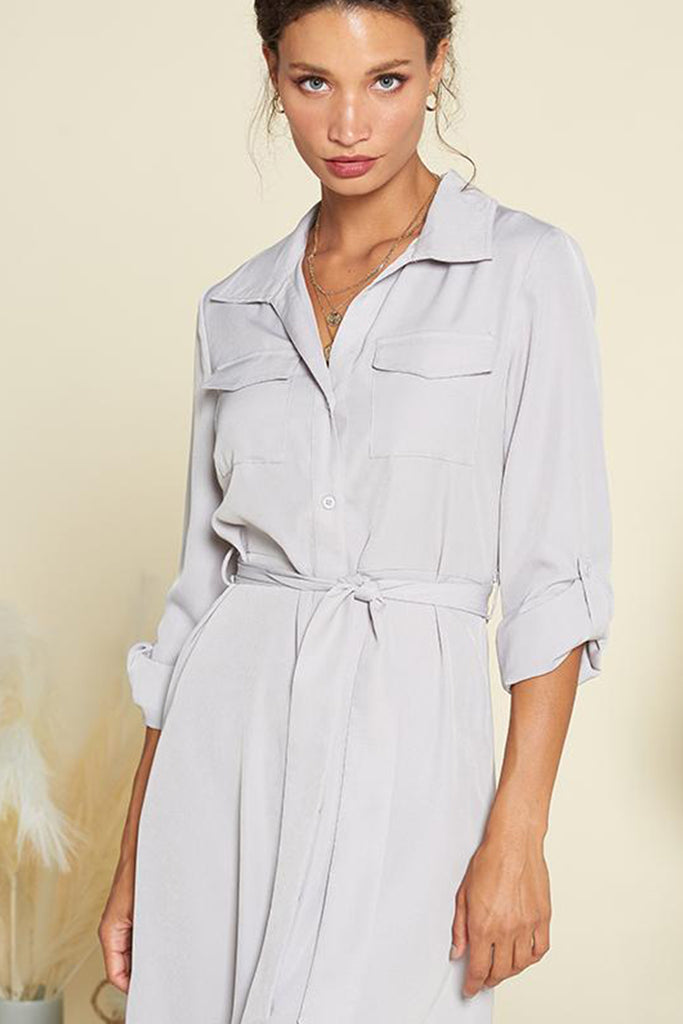 A close up of slate grey satin utility shirt midi dress with self waistband included.