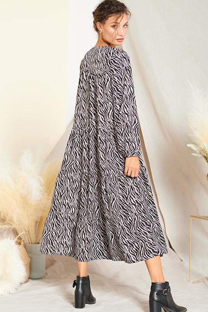 Back side of a grey zebra print midi dress with tassel spaghetti strap on open neck.