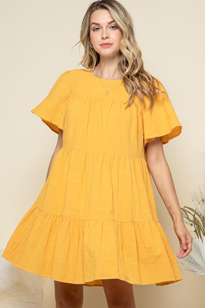 A woman wearing a mustard tiered mini dress.